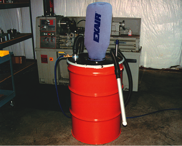 Aspiradora neumática chip vac Exair frente a un torno.