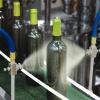 Boquilla Atomizadora de líquidos Exair aplican tratamiento a botellas antes de etiquetado.