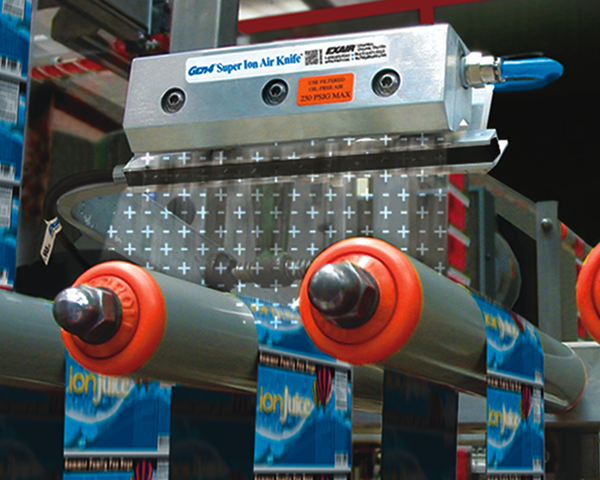 Cortina de aire Ionizado Exair ayuda a eliminar carga electrostáticas en una máquina de etiquetas plásticas generadas por la fricción con el rodillo.